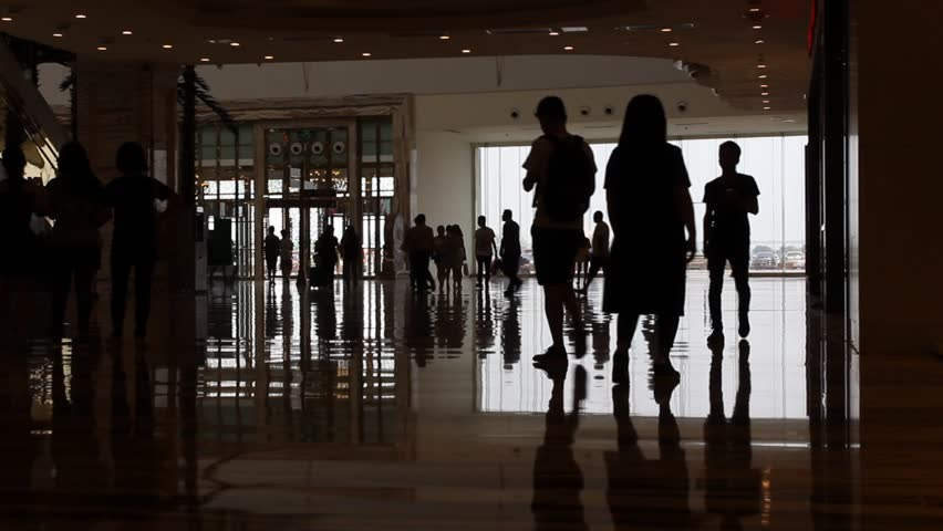 Silhouettes of people walking in the shopping mall