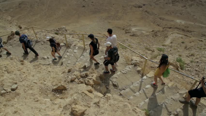 Masada, ISRAEL 15.05.2015. Group of tourists go down from high mountain.