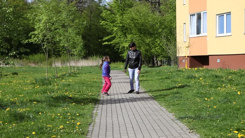 mother in a black jacket and blue jeans with her daughter in a blue jacket and red trousers walking on the track - HD stock footage clip