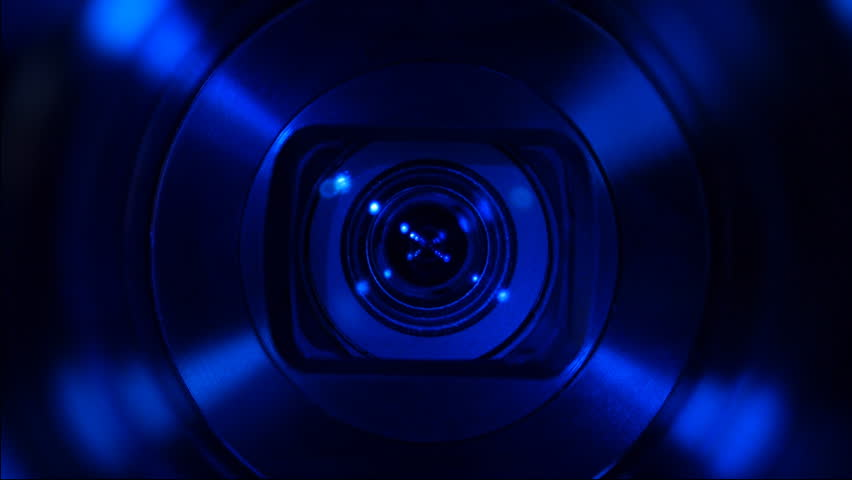Zooming camera lens in the darkness. Blue backlight. Closeup. Shallow depth of field