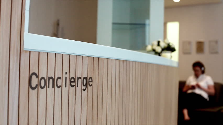 Concierge desk and waiting room. Video footage with tight focus on the word 'Concierge' mounted on the front desk to a contemporary dentist surgery with a patient waiting in the background.