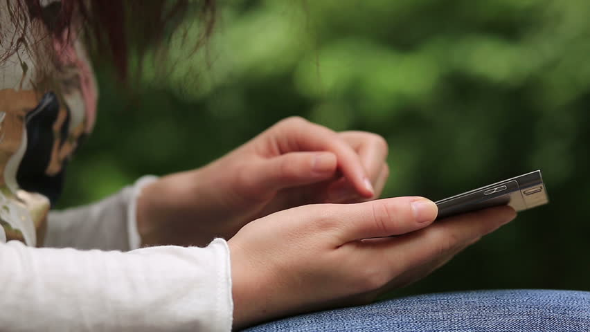 Woman uses smartphone outdoors