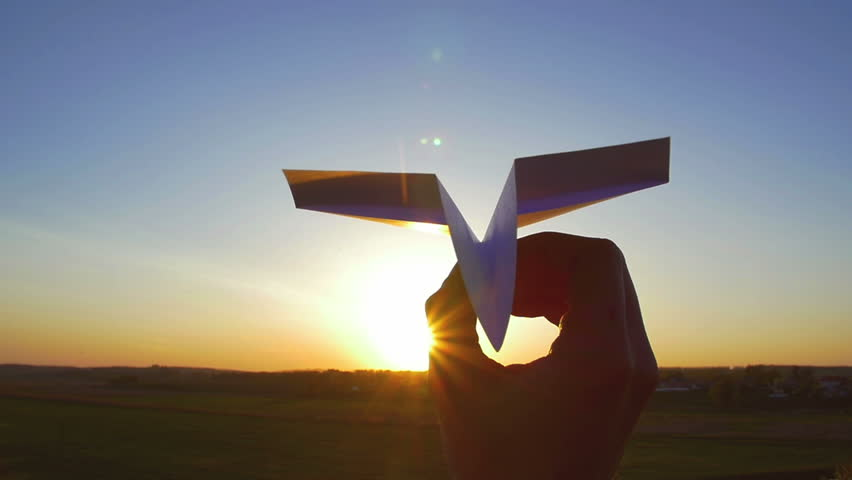 4 in 1 video! The hand hold paper airplane and launch by the bright sun and picturesque landscape background. 4x slow motion capture. Shot with Red Cinema Camera