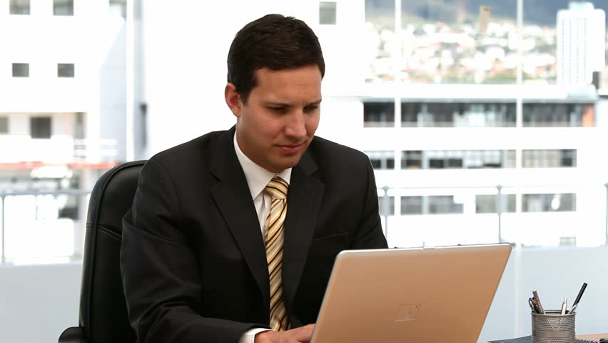 Businessman working on the laptop and looking at the camera in an office - HD stock footage clip