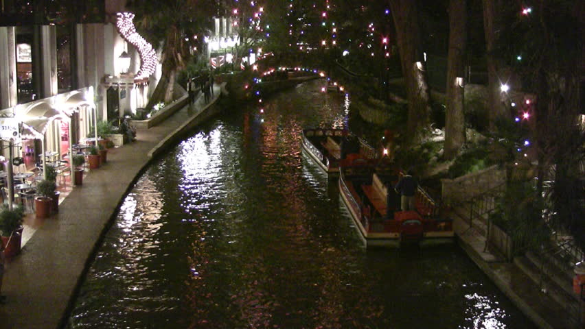 Video night Christmas lights of the San Antonio Texas Riverwalk. Tourists at restaurants and shops. Vacation area. Festive holiday atmosphere. Boats parked on shore. Foot bridge in distance. - HD stock video clip