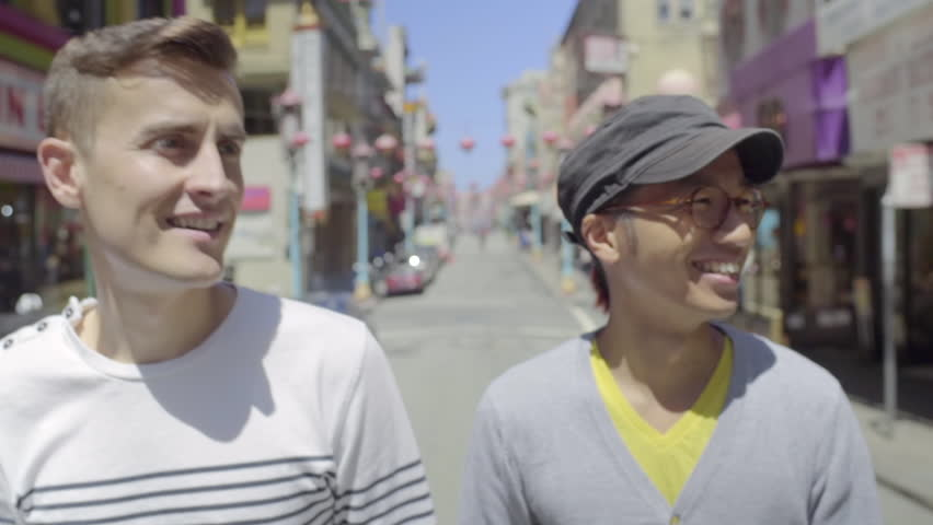 Gay Couple Walk Down A Street In Chinatown, San Francisco, They Enjoy The Sights