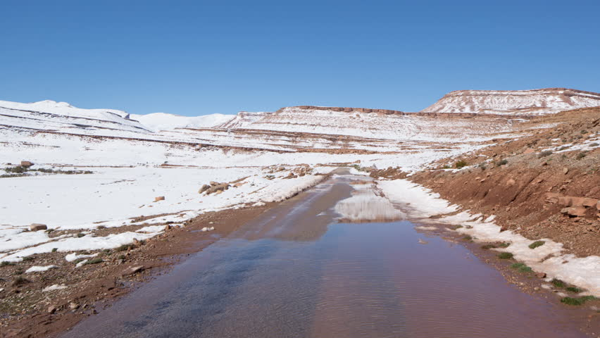 a POV shot from the front of an off road vehicle in a snowy canyon, morocco
