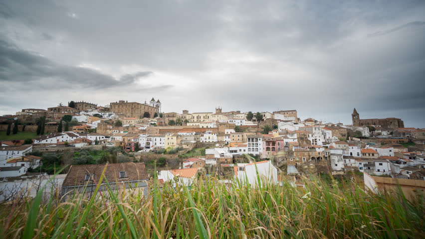 Wide angle view of Caceres against green grass, cloudy sky, 4K
