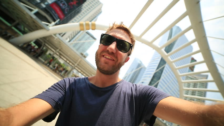 Young cheerful tourist man in Bangkok taking a selfie on the Tha Sathorn place station going to the sky train. Offices buildings and towers on the background.