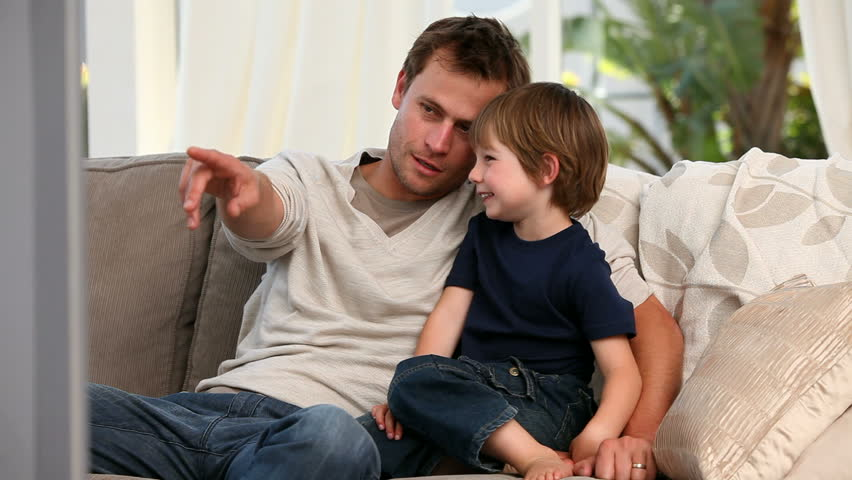 Attentive father watching tv with his son - HD stock footage clip
