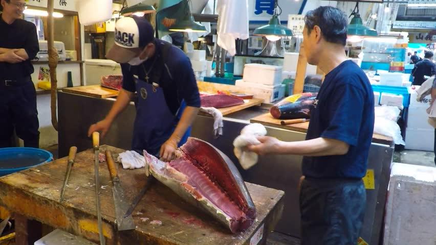 Tokyo, Japan - May 14, 2015: Fresh Tuna main cut by professional Japanese tuna handler at famous Tsukiji fish and seafood market, right after the Tuna auction. - 4K stock video clip