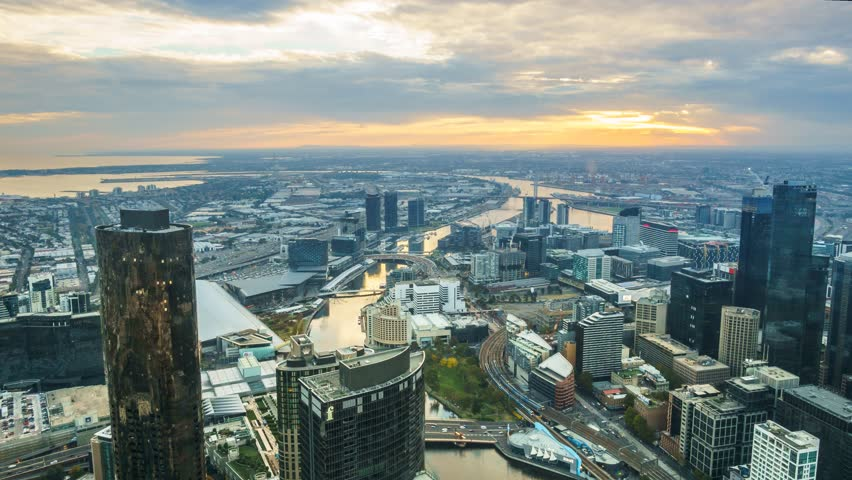 A aerial view of Melbourne cityscape including Yarra River and Victoria Harbour in the distance. Timelapse during sunset with beautiful sun ray bursting through fast moving clouds.