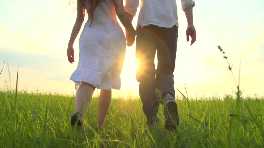 Happy Young Couple Walking on Summer field and smiling, holding hands walk through a wide field, having fun outdoors. Countryside. Man and woman on the meadow. Sun flare. Slow motion Full HD 1080p - HD stock video clip