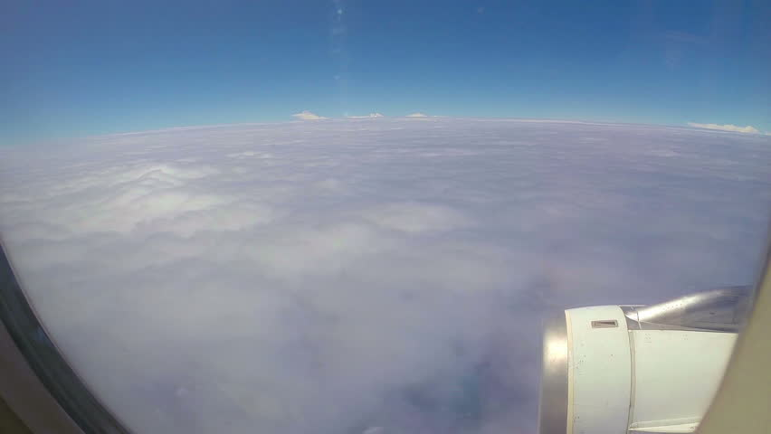 Window View. POV. Plane flight above white clouds.
