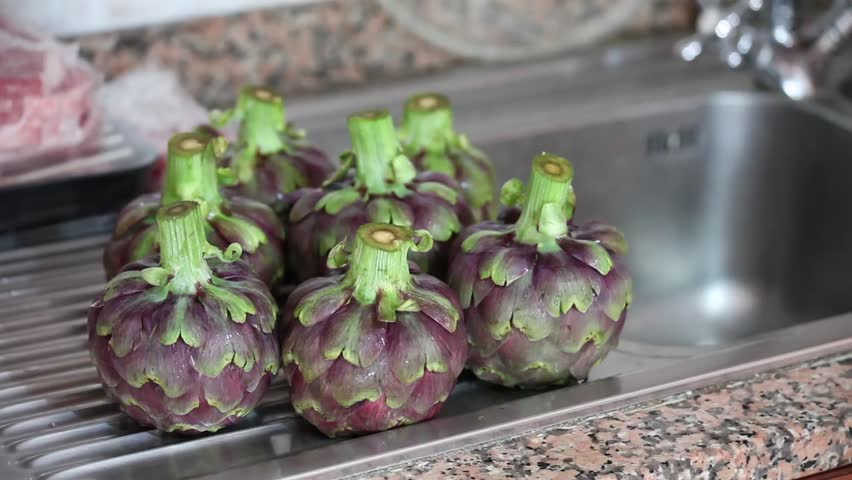 Video clip of fresh cleaned artichokes in stack on the sink.
