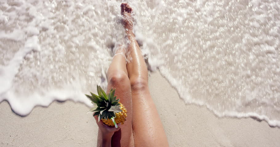 Top view of woman holding pineapple cocktail sexy legs on beach self shot