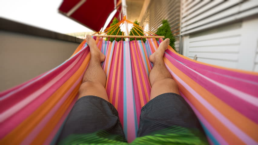 Seamless loop of a man in first person perspective lying in a hammock on a balcony moving to left and right. | Shutterstock HD Video #10215650