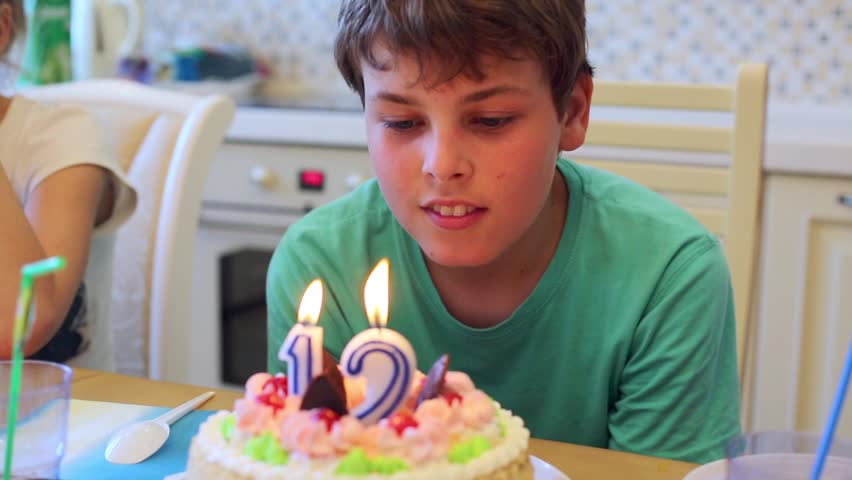 Boy sits at table with birthday cake blows up burning candles.
