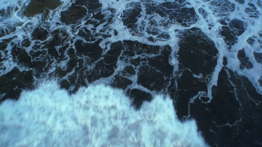 Aerial drone footage of huge waves rushing rocks. Tracking shot of tidal waves crashing. As the powerful waves break they create a texture from white sea foam. Overhead perspective. HD 1080 video. | Shutterstock HD Video #10231679