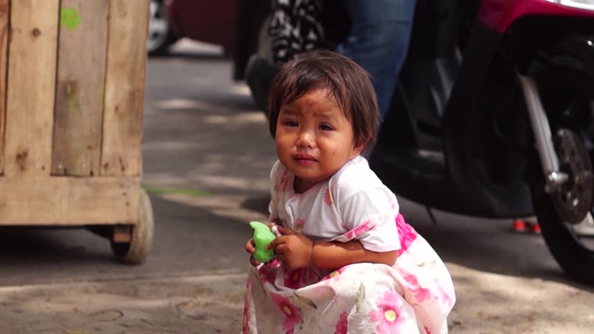 SAN PABLO CITY, LAGUNA, PHILIPPINES - MAY 8, 2015: Issues of poverty among Filipinos cause little concern to children who are left crying in the streets. Editorial