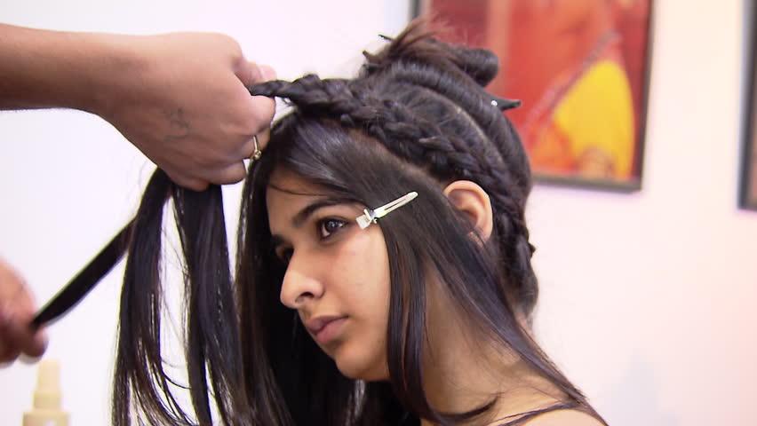 Hair dresser creating braids out of long black hair | Shutterstock HD Video #10240472