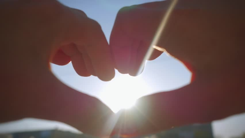 Female hands catch the sun in the sky and make a heart shape hands | Shutterstock HD Video #10245800