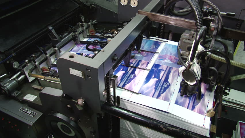 Pages being fed into a two color offset printing press. All the photographic images in this clip are property released. - HD stock footage clip