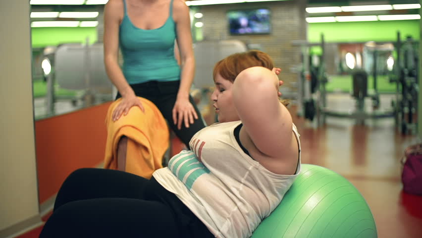 Side view of overweight lady doing situps on the fitball while her unrecognizable cropped female personal instructor watching