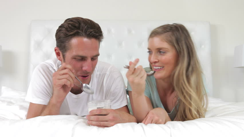 Couple lying on bed eating a spoonfuls of yoghurt and looking happy. Shot on Canon 5d Mk2 with a frame rate of 30fps - HD stock footage clip