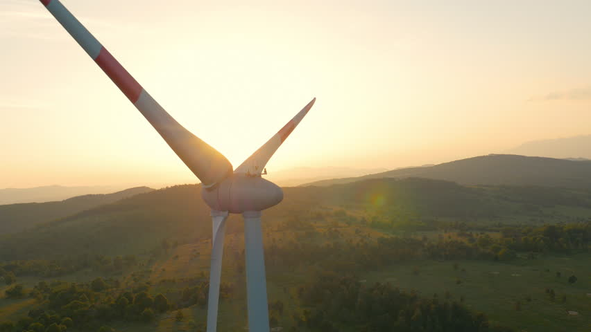 Aerial - Wind turbine blocking the sun with propeller at sunset | Shutterstock HD Video #10338158