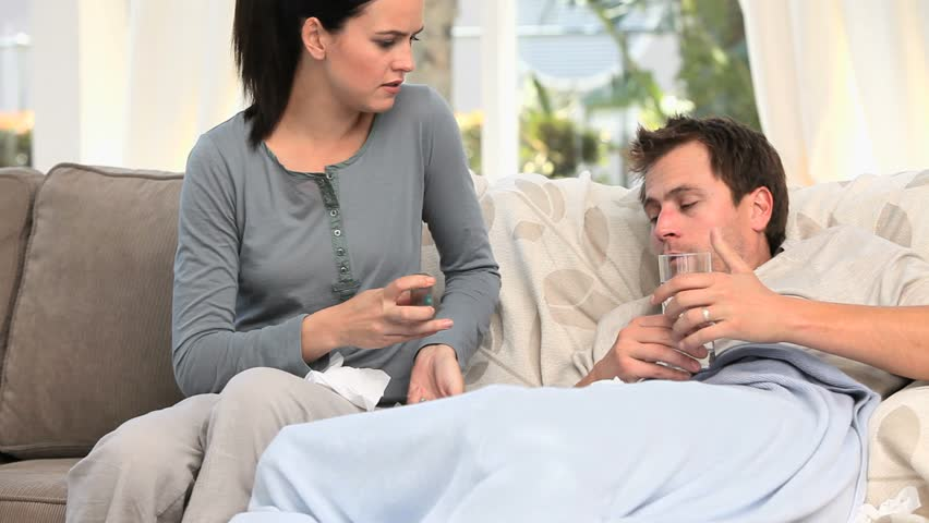 Worried Woman Giving Pills To Her Sick Husband Stock