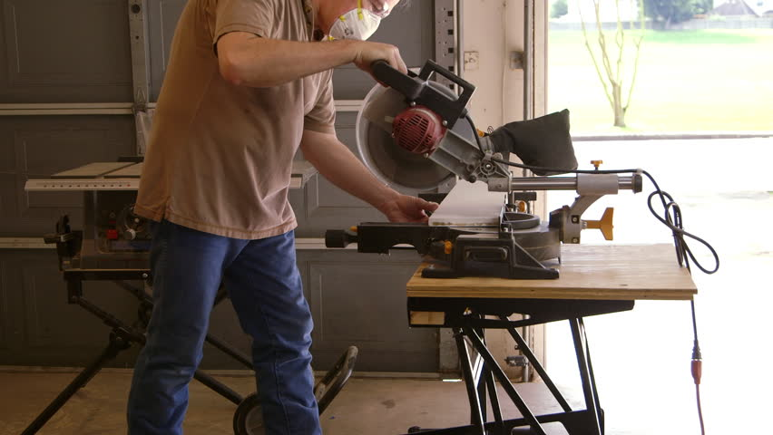 A tradesman or handyman homeowner type using a power miter saw to cut a board for a home improvement project. - HD stock footage clip
