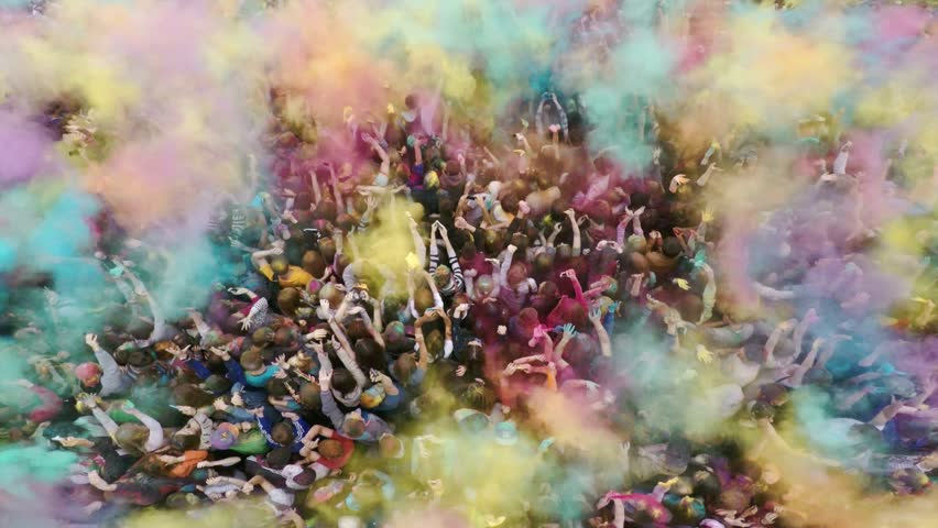 Russia, Chelyabinsk, 13 June 2015: Aerial flight above dancing crowd on Holi Festival Of Colors. Crowd of people colored powder and having fun.