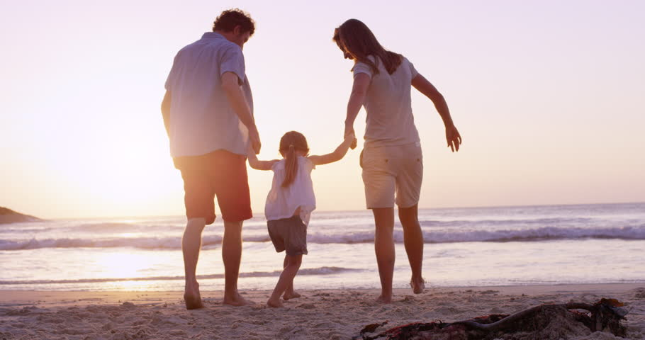 Happy family on the beach holding hands swinging little girl around at sunset on vacation slow motion RED DRAGON - 4K stock video clip