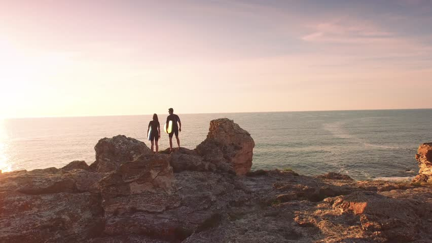Young Surfers Man Woman Walking Standing On Top Of Cliff High Five Congratulations Achievement Sports Holiday Vacation Happiness Concept - 4K stock video clip