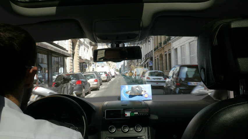 Paris, France. May 11, 2015. Car ride shot from the backseat of a taxi in Paris, while driving through small streets and alleys on a sunny day.