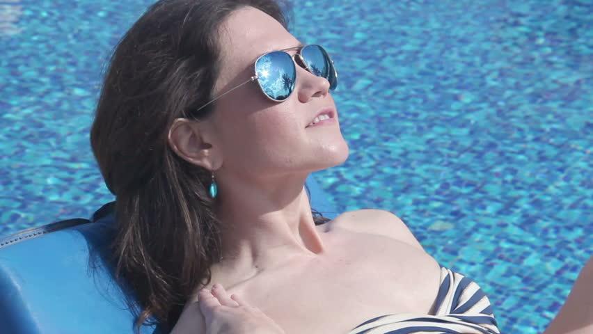 Pretty woman bikini applying tanning oil on skin, rubbing legs