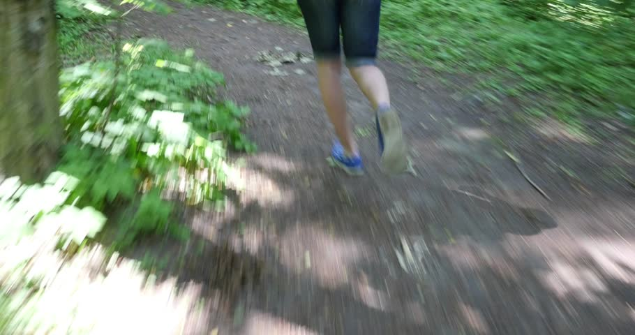 Male trail runner running in the forest on a trail.Close-up on running shoes.  - 4K stock footage clip