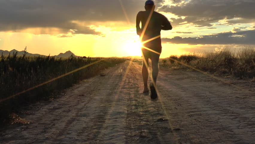 Runner jogs along dirt road cutting through farm field, his silhouette glows through bright yellow rays of setting sun. 1080p - HD stock footage clip