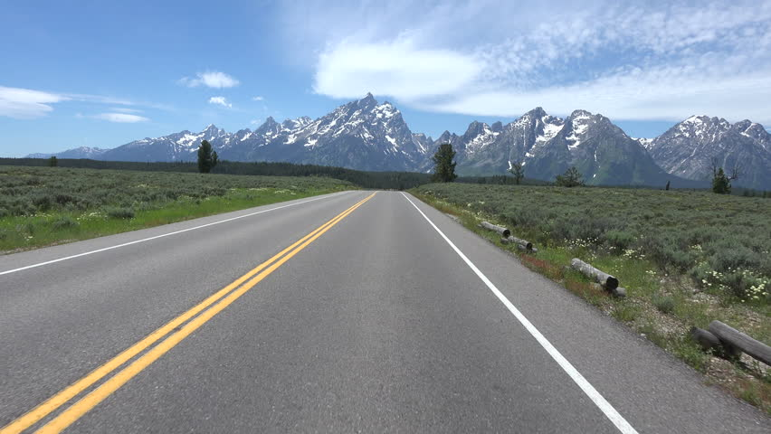 GRAND TETONS, WYOMING - JUN 2015: Driving POV towards Grand Teton NP Mountains 4K. Wyoming south of Yellowstone. Pristine ecosystem. Mountaineering, hiking, fishing and other forms of recreation. | Shutterstock HD Video #10518356