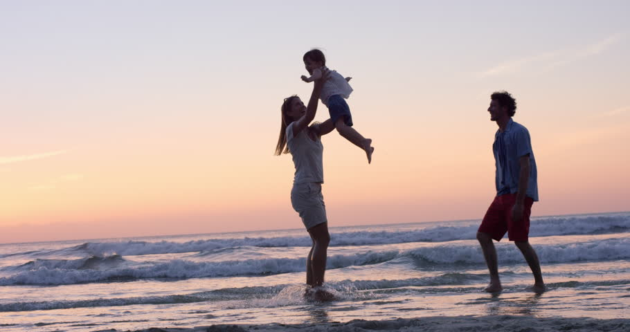 Mother swinging little girl around Happy family on the beach holding hands sat sunset on vacation slow motion RED DRAGON - 4K stock footage clip