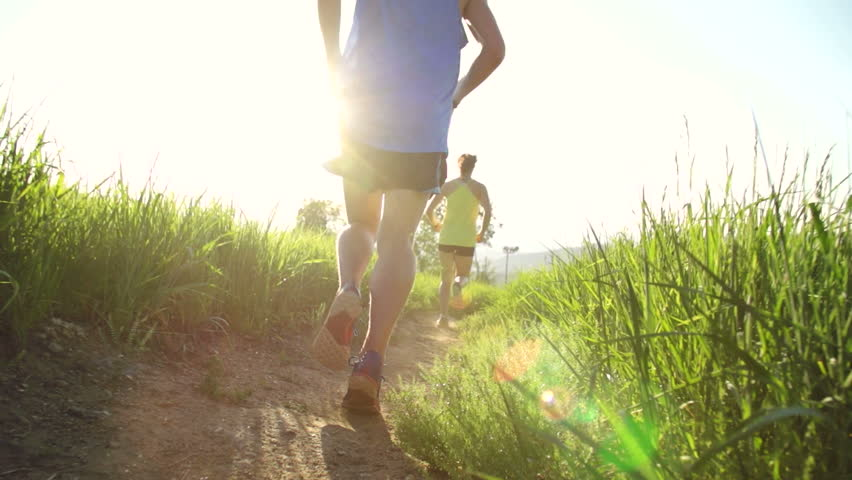 Couple Running Outside At Sunset With Lens Flare