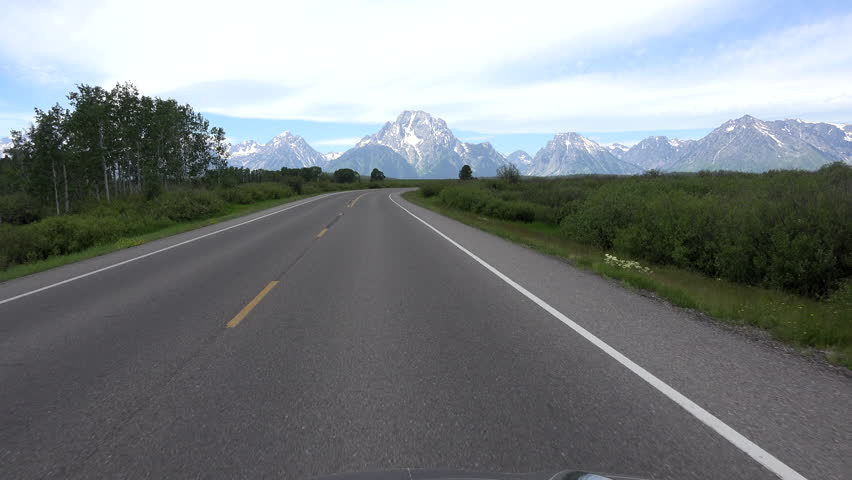 GRAND TETON, WYOMING - APR 2015:  Driving POV Grand Teton Mountains Wyoming 4K. Point of view vacation travel. South of Yellowstone. Pristine wonder and beauty. Wildlife tourism destination. | Shutterstock HD Video #10530173