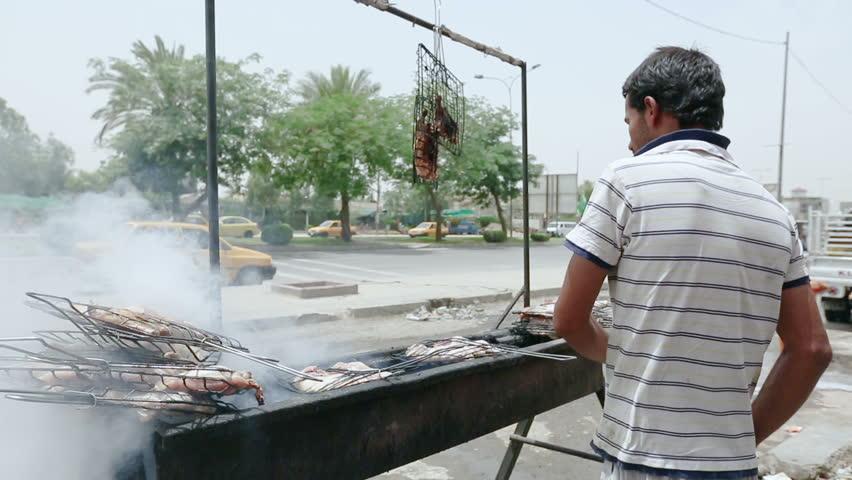 BAGHDAD, IRAQ - MAY 2015: An Iraqi man makes grilled chicken at Palestine street in Baghdad, Iraq
