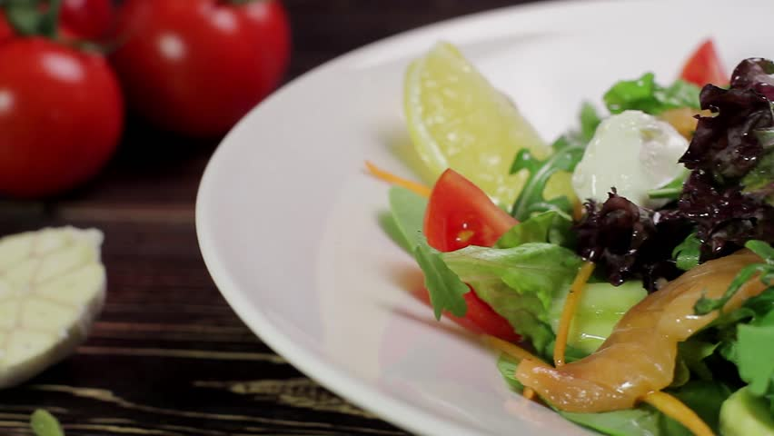 Salad with salmon, vegetables and mozzarella cheese. Pours salad with olive oil.