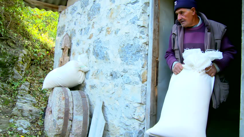 MONTENEGRO - ANDRIJEVICA 2012 - Man carries a sack of flour and exits from the mill - HD stock video clip
