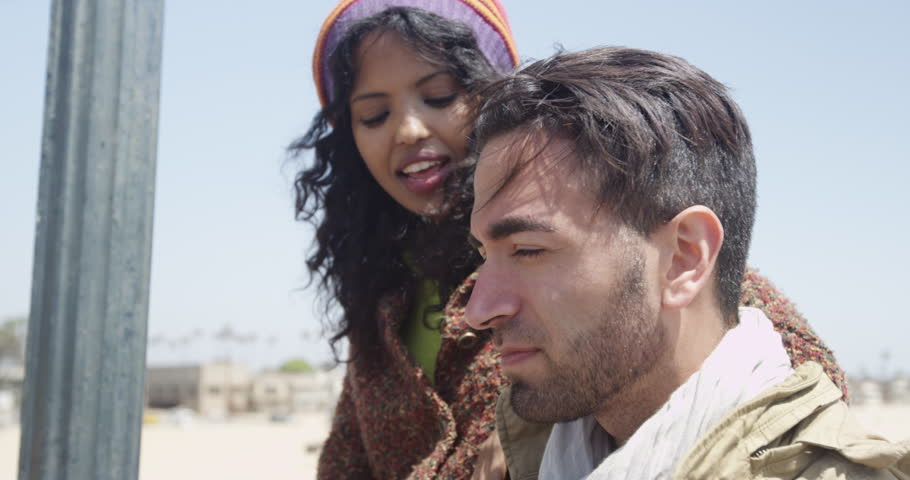 Hispanic man talking with african female friend at the beach on a beautiful summer day | Shutterstock HD Video #10564076
