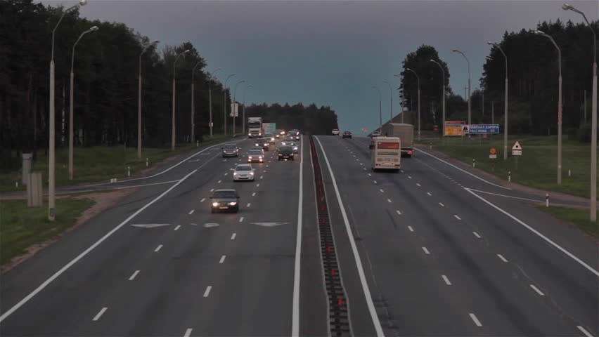 Road vehicles daily traffic. View from overpass bridge to multiple lane highway where cars and trucks are moving in both directions during the evening time - HD stock video clip