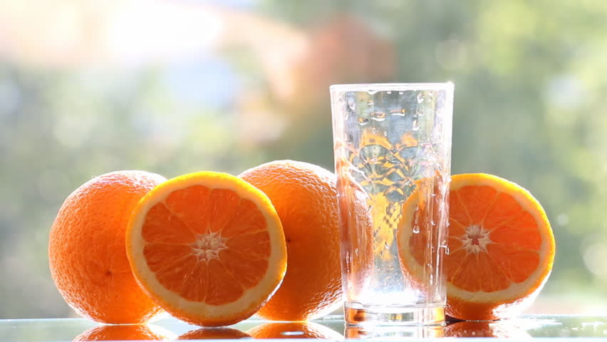 Oranges and orange juice on a green background.