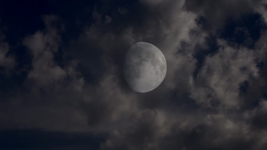 Full moon shining bright behind clouds at dark night. Time lapse - HD stock video clip
